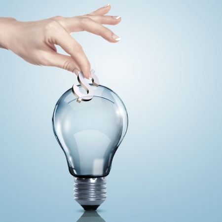 making a save: Hand and money inside an electric light bulb Stock Photo