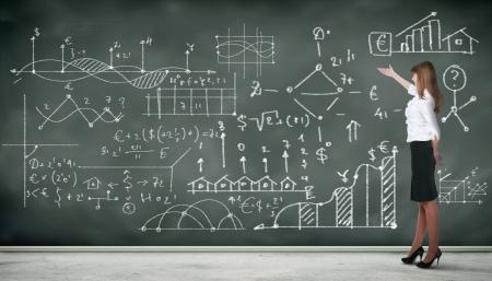 profesor: Personas de negocios de pie contra la pizarra con una gran cantidad de datos escrito en �l