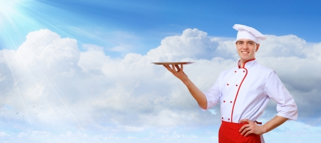 Portrait of a young male cook in red apron against colour background Stock Photo - 15765541