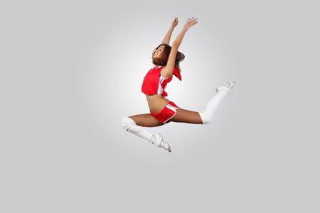 Young female dancer jumping against white background photo