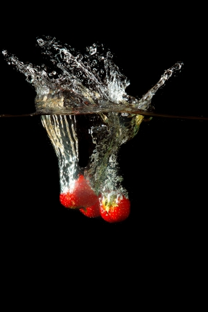 pimiento: Colored red paprika in water splashes on black background