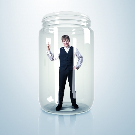 Businessman trapped inside a transparent glass jar Stock Photo - 15862613
