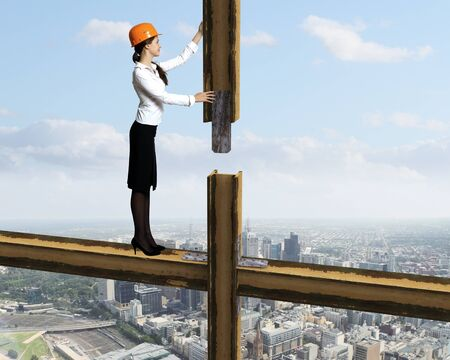Business woman standing high over a cityscape photo