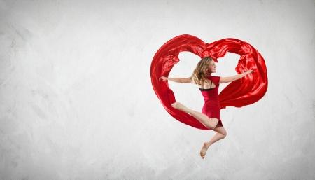 air flow: Giovane donna che balla con tessuto rosso simbolo studio e nel cuore