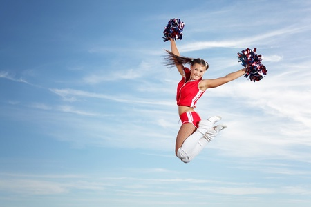 Young beautiful female cheerleader in uniform jumping high Stock Photo - 15851246