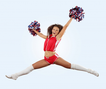 pom: Uniformed cheerleader jumps high in the air isolated on white  Stock Photo