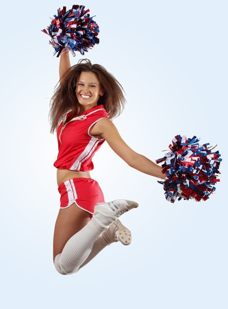 pom pom: Uniformed cheerleader jumps high in the air     isolated on white