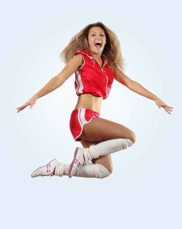 exciting: Uniformed cheerleader jumps high in the air     isolated on white
