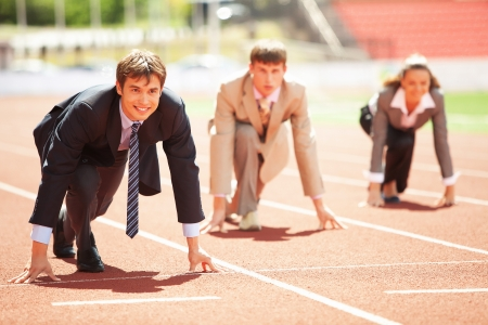 contender: Businessmen running on track racing at athletich stadium Stock Photo