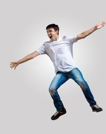 Modern slim hip-hop style man jumping dancing on a grey background photo