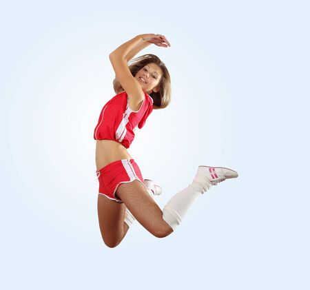 Uniformed cheerleader jumps high in the air     isolated on white