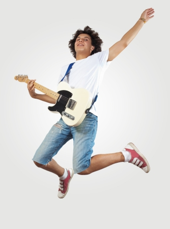 young man playing on electro guitar and jumping photo