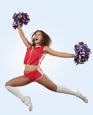 euphoric: Uniformed cheerleader jumps high in the air     isolated on white
