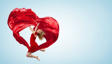 dancing woman: Young woman dancing with red fabric in studio and heart symbol