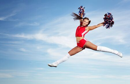 Young beautiful female cheerleader in uniform jumping high Stock Photo - 15965367