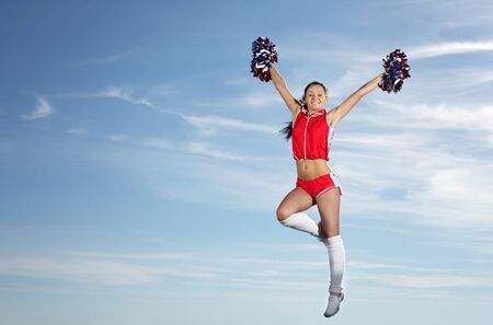 Young beautiful female cheerleader in uniform jumping high photo