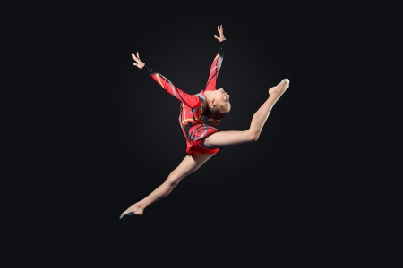 gymnastic girl: Young cute woman in gymnast suit show athletic skill on black background