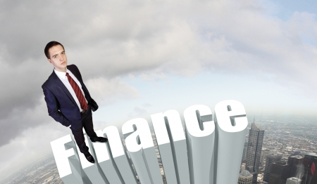 Businessman in suit standing on the word Finance photo