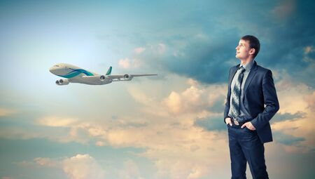Businesman and plane on the background against cloudy sky photo