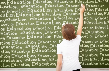 women children: Scoolgirl standing in class near a green blackboard