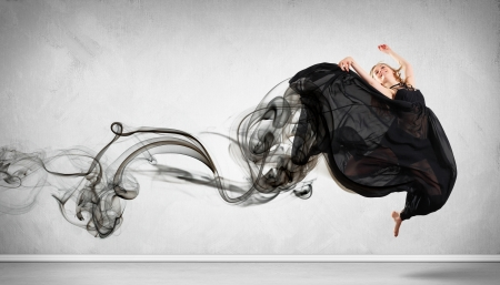 Beautiful young dancer with black smoke curles around her photo