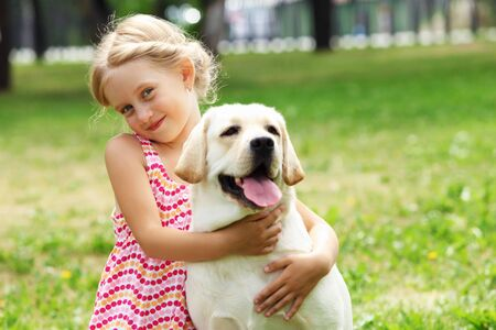 A little blond girl with her pet dog outdooors in park Stock Photo - 16142314