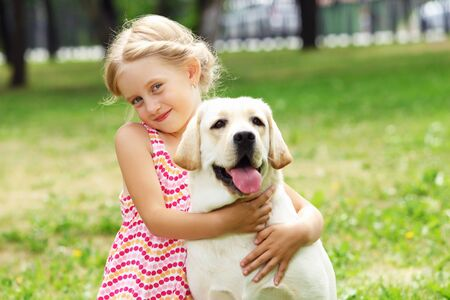 A little blond girl with her pet dog outdooors in park Stock Photo - 16142319