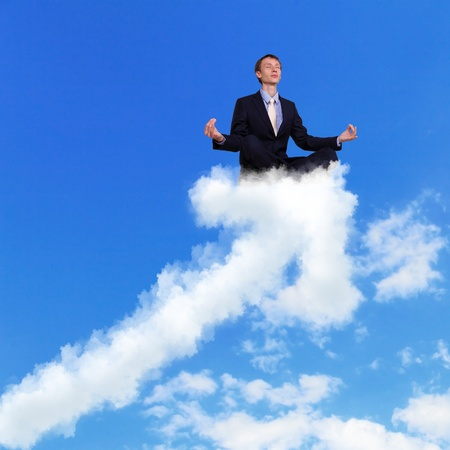 Businessman meditating sitting on the white cloud photo