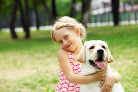 A little blond girl with her pet dog outdooors in park Stock Photo - 16142276