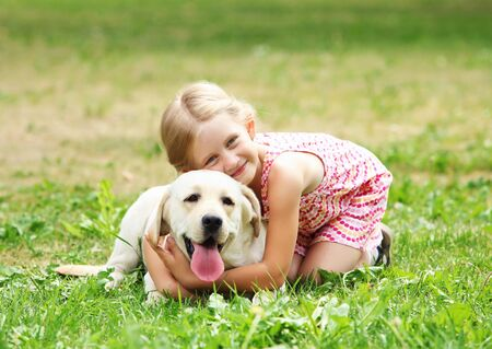 A little blond girl with her pet dog outdooors in park Stock Photo - 16142380