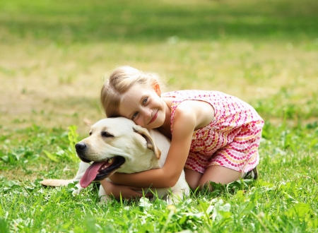 A little blond girl with her pet dog outdooors in park Stock Photo - 16142388