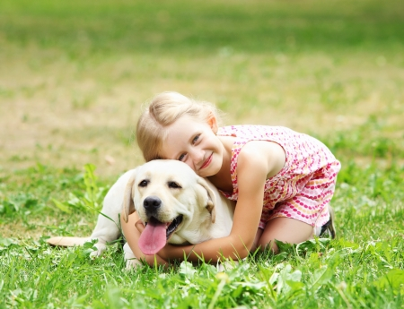 A little blond girl with her pet dog outdooors in park Stock Photo - 16142383