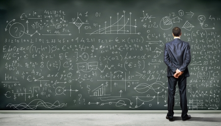 scholars: Business person standing against the blackboard with a lot of data written on it