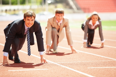 effort: Businessmen running on track racing at athletich stadium Stock Photo