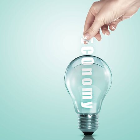 Hand putting a busines term into a light bulb photo