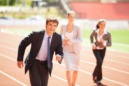 Businessmen running on track racing at athletich stadium photo