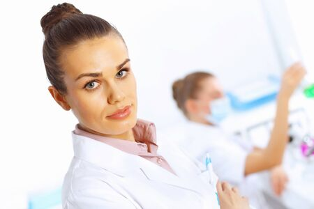 Young female doctor in white uniform with collegues on the background Stock Photo - 16192783