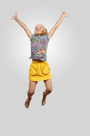 a little girl jumping and raising hands against grey background photo
