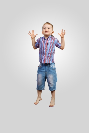 a little boy jumping and raising hands against grey background photo