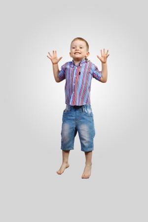 ni�o saltando: un ni�o saltando y levantando las manos contra el fondo gris Foto de archivo