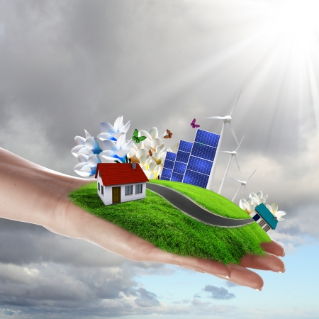 Hands holding a green earth with solar batareis Stock Photo