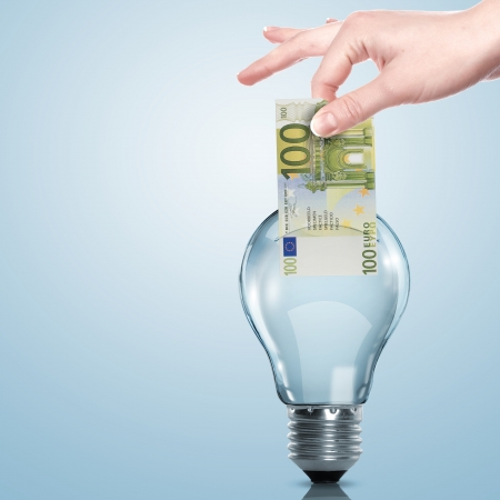 save energy: Hand and money inside an electric light bulb Stock Photo