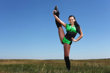 Young cheerleader in green costume jumping against blue sky photo