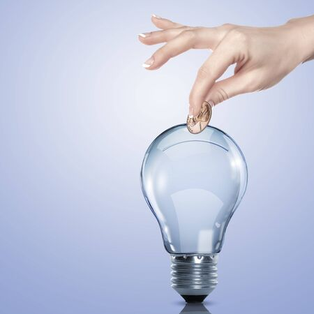 Hand and money inside an electric light bulb Stock Photo - 16226826