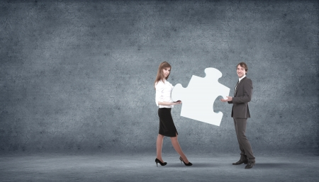 Team of business people collaborate holding up jigsaw puzzle pieces as a solution to a problem Stock Photo - 16228472