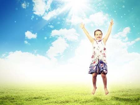 a little girl jumping and raising hands against nature background photo