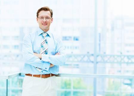 Young businessman in suit working in bright office, standing photo