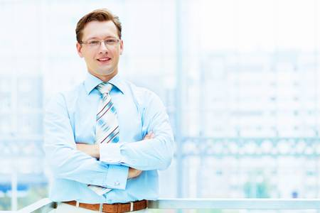 Young businessman in suit working in bright office, standing Stock Photo - 16383271