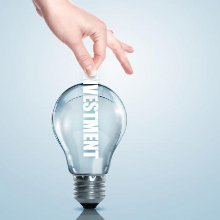 Hand putting a busines term into a light bulb photo