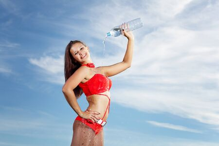 Young female sport girl in red uniform with a bottle of water Stock Photo - 16352654